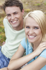 Portrait of smiling young woman with man relaxing in park