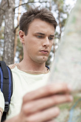 Handsome young man with backpack reading map in forest