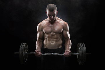 Young muscular man lifting weights over dark background