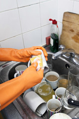 Cropped image of woman's hands washing cup at kitchen sink