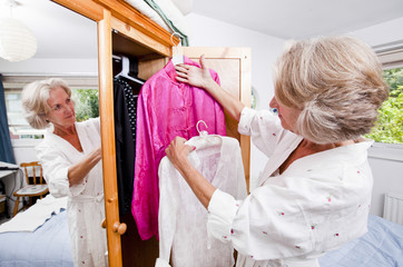 Senior woman choosing dress from closet at home