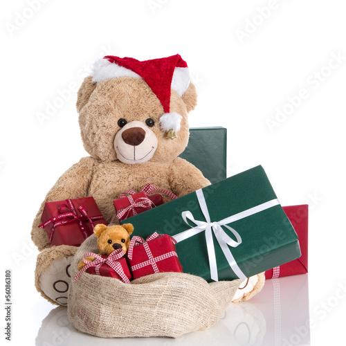 Teddybär mit einem Sack Geschenke isoliert in Grün und Rot