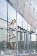 Full length of happy young businesswoman using cell phone at office balcony