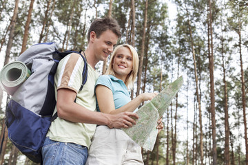 Happy young backpackers reading map in woods