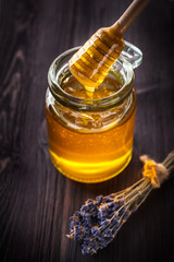 Honey dripping from a spoon in a jar and a bouquet of lavender