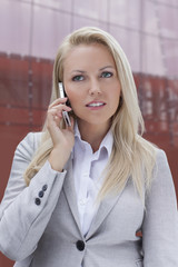 Young blonde businesswoman communicating on mobile phone against office building