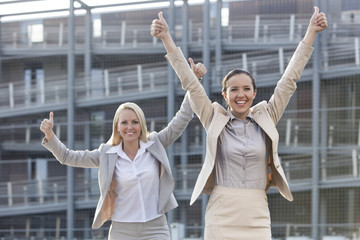 Excited young businesswomen gesturing thumbs up against office building