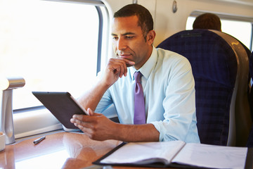 Businessman Commuting On Train Using Digital Tablet