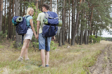 Full length rear view of young hiking couple holding hands in countryside