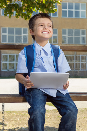Little boy on his first day at school with tablet