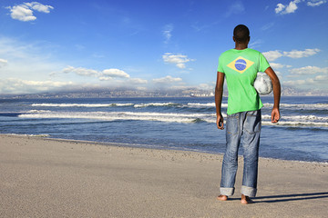Rear view of man standing wearing Brazilian t shirt with football on a beach