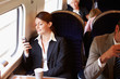 Businesswoman Commuting To Work On Train Using Mobile Phone