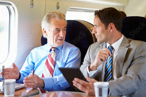 Two Businessmen Having Meeting On Train