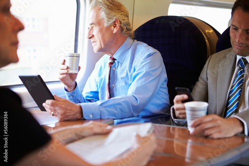 Businessman Relaxing On Train With Cup Of Coffee