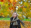 The beautiful woman in autumn park throws up red maple leaves..
