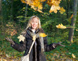 woman in autumn park with an armful of maple leaves