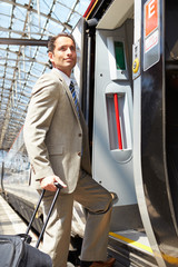 Businessman Getting On Train At Platform