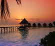 Silhouette of lodges in the sea at sunset. Maldives