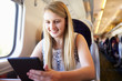 Teenage Girl Using Digital Tablet On Train Journey