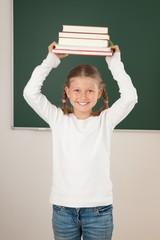 Schülerin stemmt Bücherstapel hoch