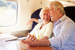 Senior Couple Relaxing On Train Journey - 56093917