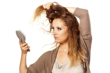 unhappy girl combs her hair and looking at the damaged ends