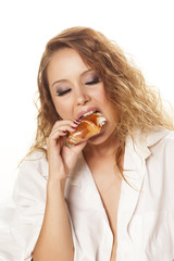 pretty hungry girl in white shirt voraciously eating donut