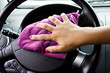 Woman's hand with microfiber cloth polishing wheel of a car
