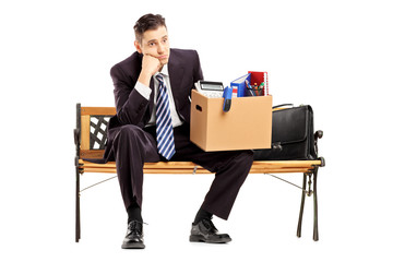 Disappointed businessman in a suit sitting on a bench with a box