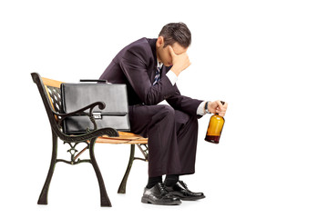 Disappointed businessperson sitting on a bench with a bottle