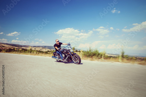 Young biker riding a motorcycle on an open road