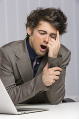 Overworked exhausted businessman yawning at work.