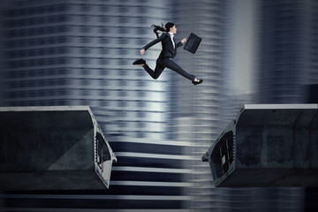 Businesswoman jumping over a gap in the bridge