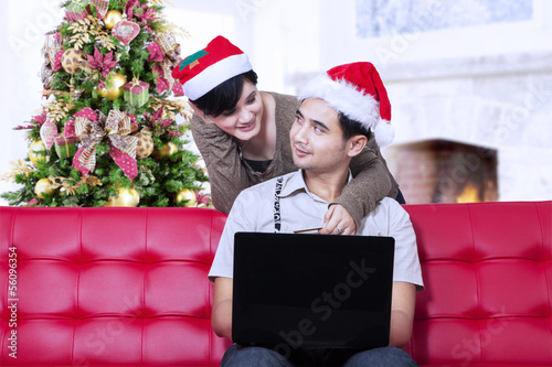 Couple buying christmas gift online at home