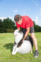 Dog stretching over yoga ball