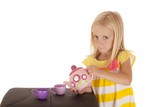 Darling young blond girl playing with a tea set poster