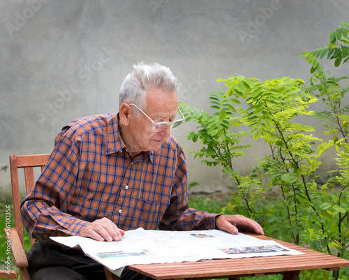 Pensioner reading newspaper in garden