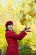 woman  throwing  maple leaves in autumn