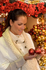 Smiling woman holding Christmas balls at shop