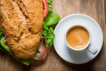 Espresso and bun with ham for breakfast