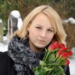 Frau mit Rosen auf Friedhof