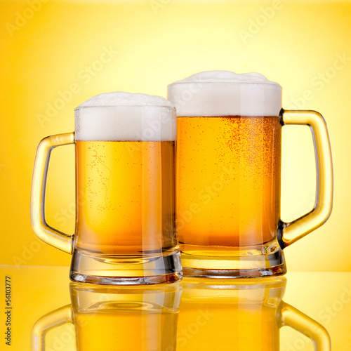 Two Mugs of fresh beer with cap of foam, isolated on yellow back