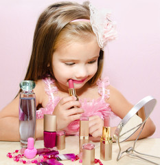 Child cosmetics  Cute little girl with lipstick and  mirror