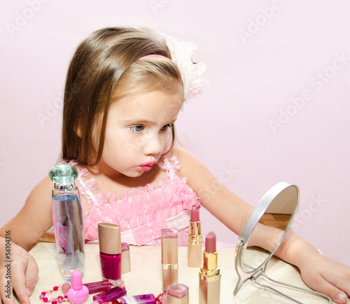Child cosmetics  Cute little girl looking in the mirror