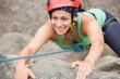Happy girl climbing rock face
