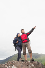 Couple standing on a rock looking up at the mountains