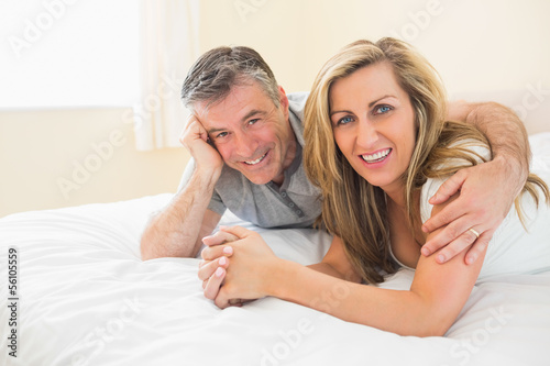 Happy couple lying on a bed looking at camera