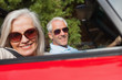 Side view of cheerful mature couple driving red cabriolet