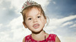 Girl in a tiara on a background of clouds