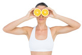 Fit woman holding slices of orange on her eyes